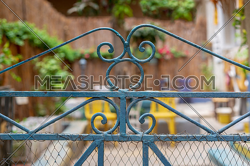Vintage artistic green wrought iron gate with peeling paint and rust revealing blurred garden in the background