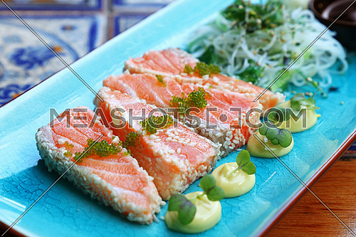 Close up portion of fresh raw salmon fish sashimi with sesame seeds, salad and soy sauce on blue plate, high angle view