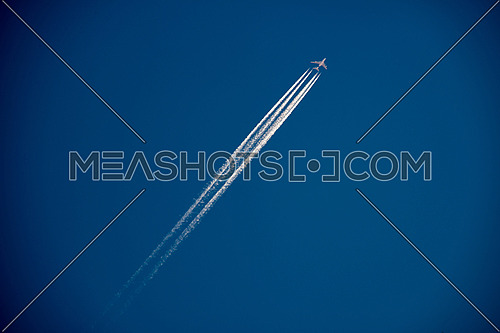 A 4 engine jetliner at cruise altitude with contrails