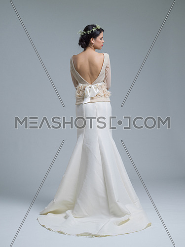 Rear view of a beautiful young bride in a wedding dress isolated on a white background