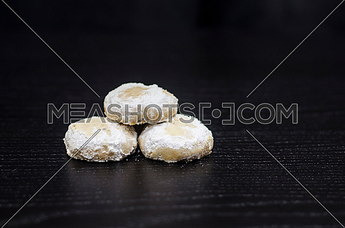 3 cookies (kahk)on a black table, 2 kahks at the bottom and one on top