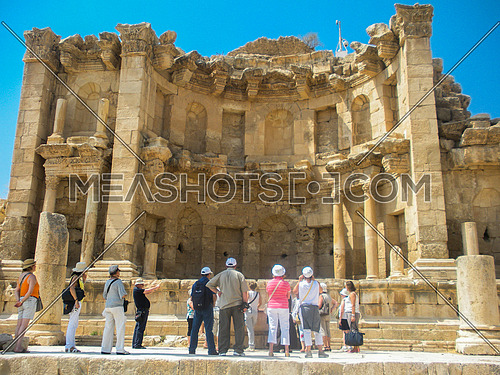 A group of Tourists gathered around a historical monument in Jarash , Jordan