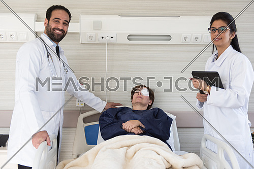 Middle eastern doctors and happy patient at eye clinic in a large modern hospital