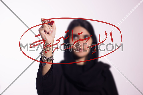 """Arabian middle eastern business woman writing with a marker on virtual screen in arabic """"Strategy"""" isolated on white background"""