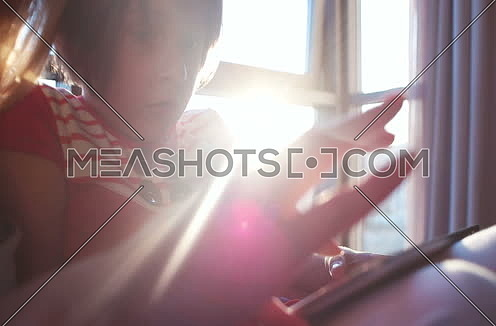 Mother And Daughter Using A Tablet  at home with sun rays coming from window