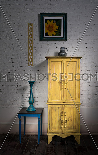 Still Life of  vintage yellow cupboard, framed painting, blue candlestick and vintage small table on dark wooden floor and white bricks wall in Studio
