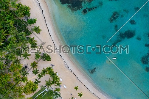 Aerial view of tropical beach with white boat anchored.Samana peninsula,Bahia Principe beach,Dominican Republic.