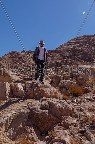 Long Shot group of tourists climb down rocks explore Sinai Mountain for wadi Freij at day.