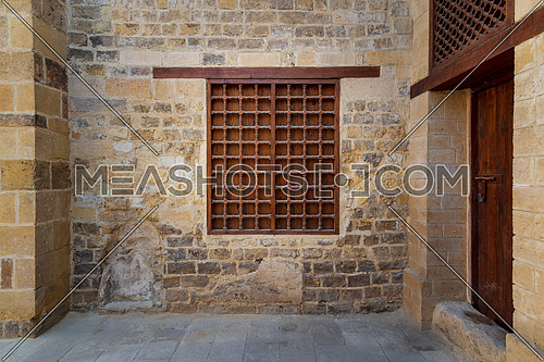 Mamluk era wooden closed window with wooden ornate grid over stone bricks wall, Tekkeyet Al Bustami, Dar El Labana district, Cairo, Egypt