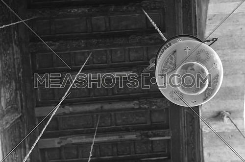 A ceiling lamp with islamic writings hanged in an old mosque, black