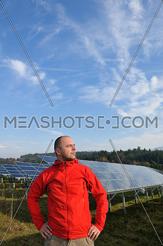Male engineer at work place, solar panels plant industy in background