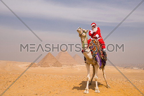 santa claus riding a camel in the pyramids desert in egypt