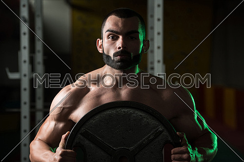 Portrait Of A Physically Young Man Holding Weights In Hand In A Dark Gym