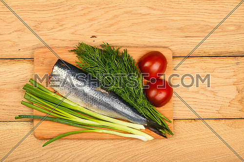 Herring double fillet with onion, dill and tomatoes on bamboo board on vintage wooden table surface
