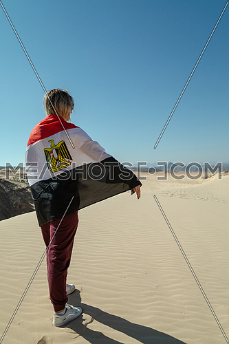 Female tourists spreading Egyptian flag while exploring Sinai Trail from Ain Hodouda by day.