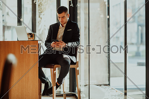Happy businessman sitting at the cafeteria with laptop and smartphone. Businessman texting on smartphone while sitting in a pub restaurant. Businessman working and checking email on the computer.