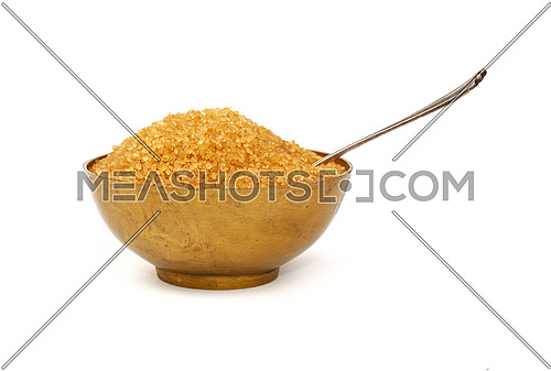 Close up one vintage bronze metal bowl full of raw brown cane sugar with antique spoon, isolated on white background, low angle side view