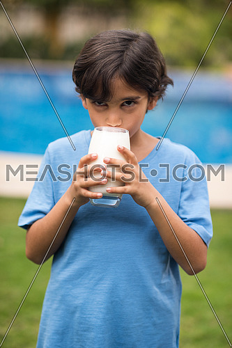 Middle Eastern boy enjoying with a glass of milk in his hand outside on summer day