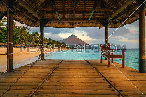 Wonderful view across the pier, on the left the tropical beach and in the background a beautiful mountain illuminated by red during sunset, Mauritius
