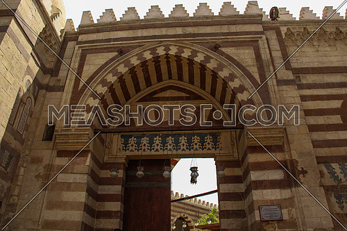 a photo for the entrance gate of the blue mosque (sonkor) in old Islamic Cairo , Egypt showing the architecture style used