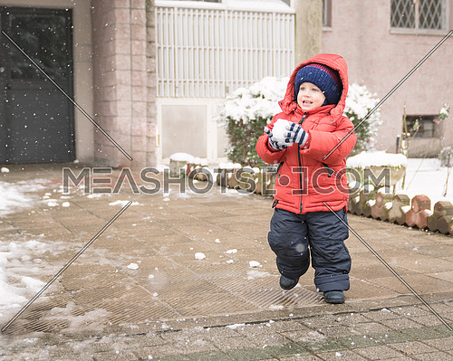 Baby boy while it snows runs with a snowball in his hands