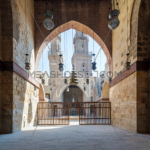 Huge arch revealing courtyard of Mamluk era Sultan Al Nassir Qalawun mosque with two minarets at the far end, Moez Street, Cairo, Egypt