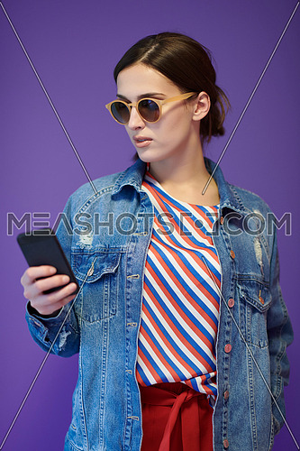 Portrait of young girl using smartphone while standing in front of purple background. Female model wearing sunglasses representing modern fashion and technology concept