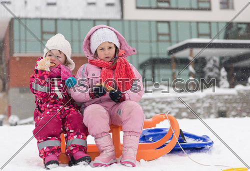portrait of two cute little grils sitting together on sledges outdoors at snowy winter day, eating tasty cookies on break