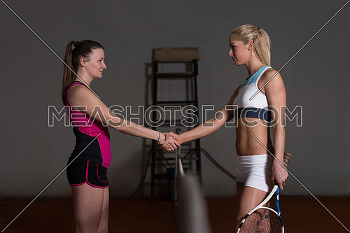 Two Beautiful Female Tennis Players Holding Rackets And Shaking Hands Over The Net - Isolated On Black
