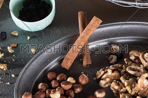 Dry nuts in a metal tray and a blue bowl with raisins and cinnamon sticks
