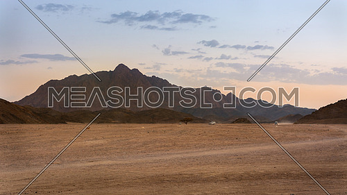 In the picture three jeeps while crossing the desert rocks Egyptian at sunset.