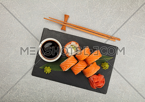Close up set of six Philadelphia sushi rolls with raw salmon served on black slate board, elevated top view, directly above
