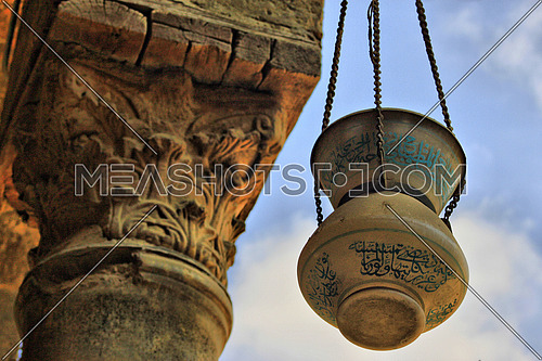 An old glass Lamp hanged beside a pillar, old architecture against blue sky