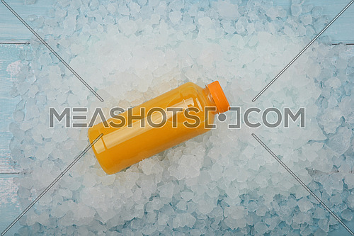 Close up one plastic PET bottle of fresh orange juice over background of crushed ice, elevated high angle view, directly above