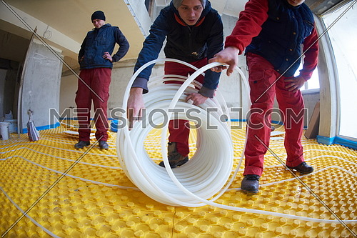grouo of workera installing underfloor heating and colling in modern home