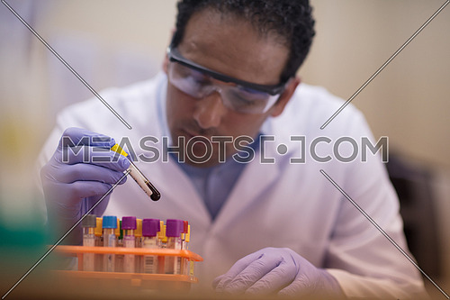 Young middle eastern man doing a bit of research testing the samples in modern laboratories
