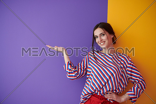 Portrait of happy smiling young beautiful woman in a presenting gesture with open palm isolated on purple and yellow background. Female model in modern fashionable clothes posing in the studio