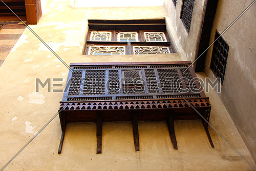 a photo from an ancient house in Islamic Cairo showing the special architecture used at that time and wooden windows