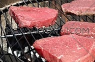 Raw beef bbq steaks cooking roasting on outdoors flame barbecue grill, one being put on fire and poured dredged with salt, close up