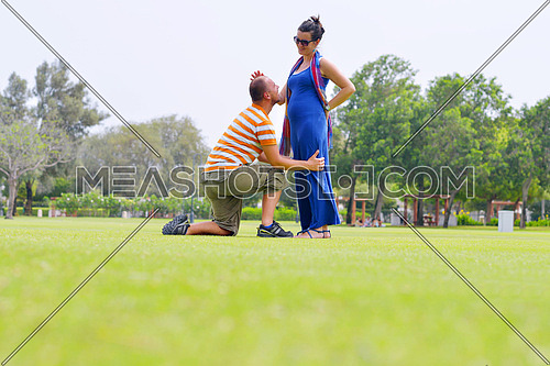 Happy pregnant woman with his husband at beautiful sunny day in park