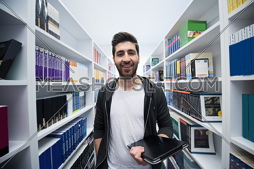 portrait of student in school  library with tablet computer. Database and archive management business concept