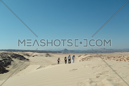 Group of tourists walking on sands with bedouin guide while exploring Sinai Trail from Ain Hodouda at day.