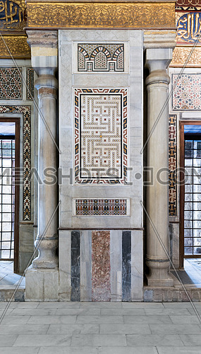 Architectural detail of an old historical decorative calligraphy mosaic colored panel between two marble columns, Mosque of Sultan Qalawun, Cairo, Egypt