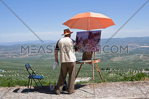 man painting on canvas near the castle of Sabiote, Spain