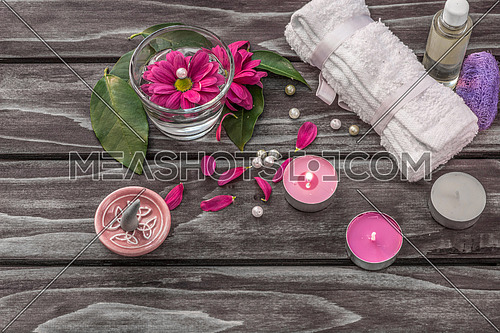 Spa concept. Lavender oil, flowers,cadles and bath white towels on wooden background.