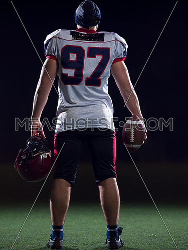 rear view of young confident American football player on field at night