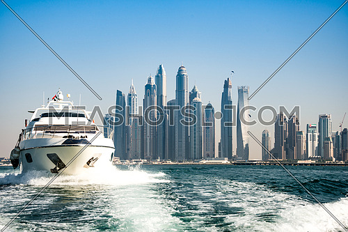 a luxury yacht infront of dubai marina waterfront