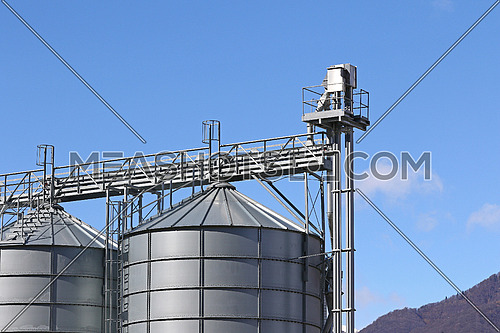 Top of agricultural storage silos against blue skies