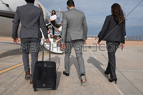 young successful middle eastern businessmen with a suitcase walking in front of private airplane