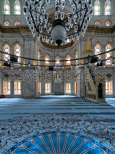 Interior shot of Nuruosmaniye Mosque, an Ottoman Baroque mosque, overlooking niche (Mihrab) and marble minbar (Platform) facade with many colored stained glass windows, Istanbul, Turkey
